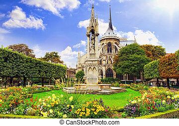 Notre Dame de Paris Cathedral, garden with flowers. Paris. ...