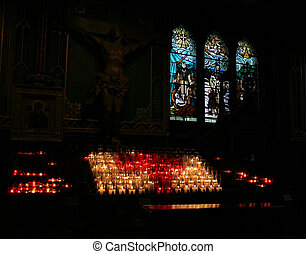 Beautiful interiors of Notre Dame Montreal, featuring a sculpture of Jesus on the cross, stain glassed windows and candles.