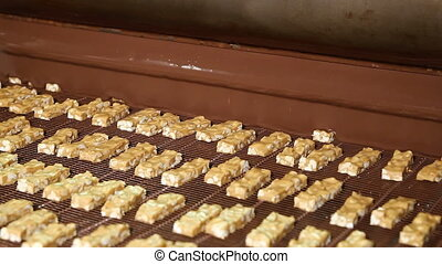 Nougat with nuts and chocolate in the factory - Bars of...