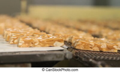Bars of nougat with peanuts on the production line - Nougat...