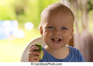 nourrisson, sien, main, regarder, appareil photo, concombre, rire, adorable, gosse