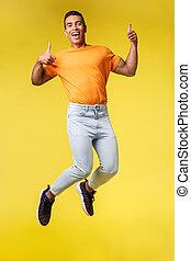 nouvelles, masculin, t-shirt, impressionnant, hipster, pantalon, vertical, joie, pouces-vers haut, geste, gai, branché, plein-longueur, sourire, approbation, blanc, exposition, célébrer, sauter, type, orange, bonheur, coup