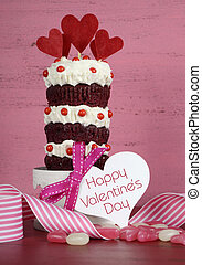 Novelty triple layer red velvet cupcake on white cake stand with ribbons and candy against a vintage shabby chic pink and red wood background, with Happy Valentines Day greeting gift tag and sample text, vertical.