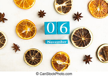 November 6. Blue cube calendar with month and date on wooden background.