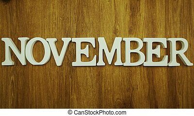 november alphabet letters on wooden background