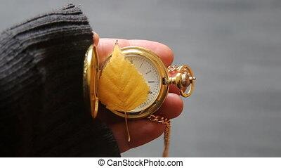 November idea. Gold pocket watch and autumn leaf.