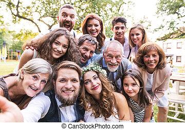 novia, novio, con, huéspedes, toma, selfie, en, recepción wedding, exterior, en, el, backyard.
