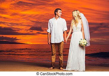 novia y novio, el gozar, asombroso, ocaso, en, un, hermoso, playa tropical, romántico, matrimonio, manos de valor en cartera