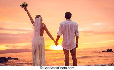 novia y novio, el gozar, asombroso, ocaso, en, un, hermoso, playa tropical, romántico, matrimonio, manos de valor en cartera, apenas casado