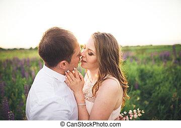 novia y novio, rissing, en, ocaso, en, un, hermoso, campo, con, flores, romántico, matrimonio