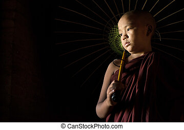 Novice with umbrella - A Young novice monk holding an...