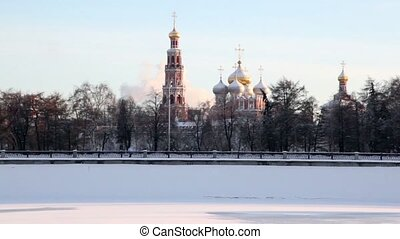 Novodevichy Convent among trees on embankment in winter,...