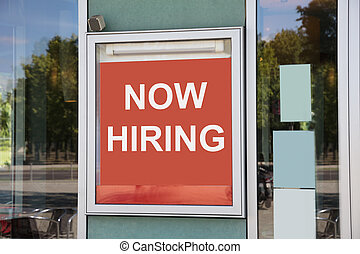 Closeup of now hiring sign outside modern office building