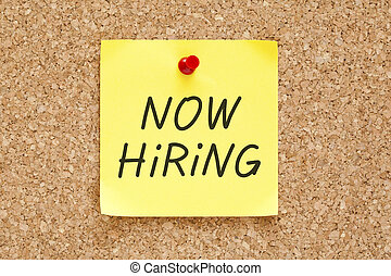 Now Hiring written on an yellow sticky note pinned with red push pin on cork bulletin board.