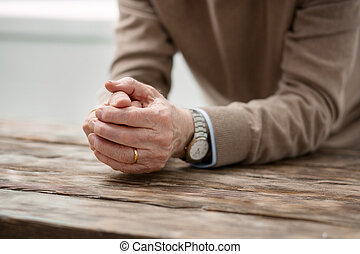 Hands of a cheerless aged man
