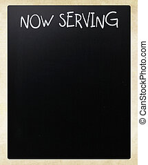 """Now serving"" handwritten with white chalk on a blackboard"