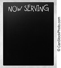 """Now serving"" handwritten with white chalk on a blackboard"