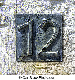 Bronze cast house number twelve on a plastered wall