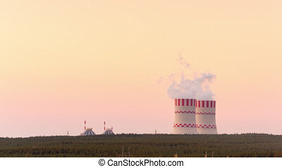 Nuclear power plant cooling towers at sunset. Time Lapse. Smoke comes from the chimneys.