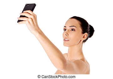 Nude beautiful woman taking selfie on white background.