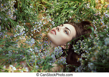Nude sexy attractive adult woman outdoors laying on flower...