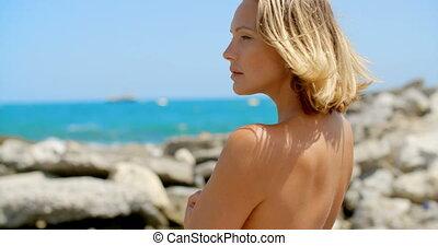 Nude Woman Enjoying View of Ocean on Rocky Beach