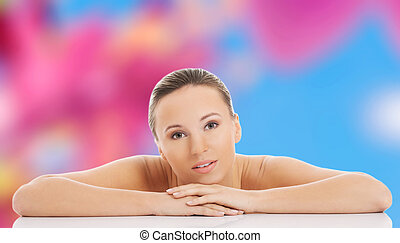 Nude woman posing with arms on desk
