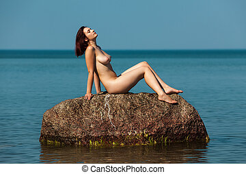 nude woman sitting on a rock in the sea