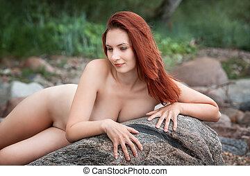 nude woman sitting on stone