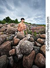 Nude woman sitting on stones