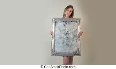 Nude Woman standing behind vintage mirror