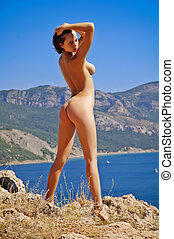 Nude woman standing on a rock