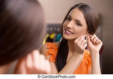 nuevo, earrings., hermoso, mujer joven, poner, ella, nuevo, pendientes, y, sonriente, mientras, el mirar, el, espejo