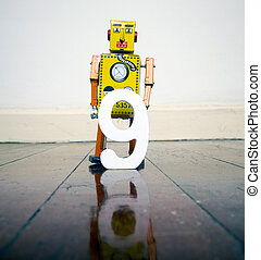 numbe 9 robot toy on a woden floor with reflection
