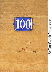 Number 100 - House Number hundred sign at stone wall