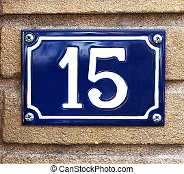 The number 15 in white on a vibrant blue metal plaque screwed to a concrete outdoor wall.