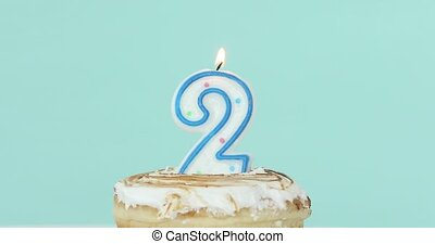 Number 2 candle in cake on pastel blue background