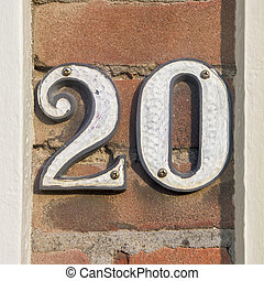 Number 20 - Ceramic house number twenty on a brick wall.