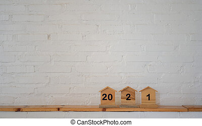 Number 2021 on a wooden house model with white brick background.