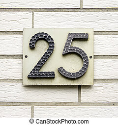 Number 25 - wrought house number twenty five on a wall of...