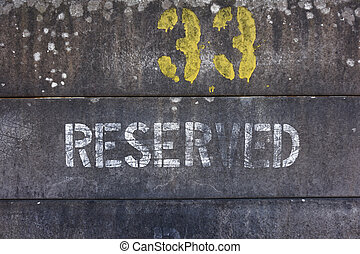Number 33 and reserved spray painted on concrete fence blocks