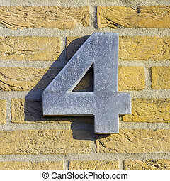 Number 4 - aluminum house number four on a yellow brick wall