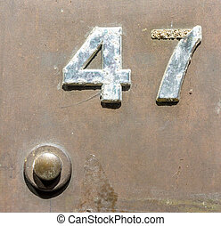 Number 47 - Wheathered house number forty seven (47) next to...