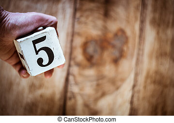 Number 5 - a hand holding a white block with number five over vintage wooden table