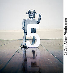 number 5 robot toy on a woden floor silver