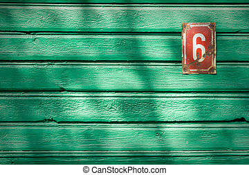 Number 6 on textured green wooden wall with a shadow