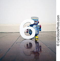 number 6 robot toy on a woden floor with reflection
