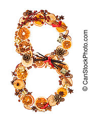 """Number """"8"""" made of Christmas spices, dry orange and apple slices and small gifts. Isolated on white background"""