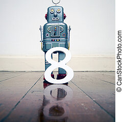 number 8 robot toy on a wooden floor with reflection grey