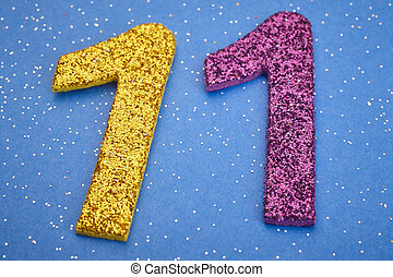 Number eleven yellow purple color over blue background. ...